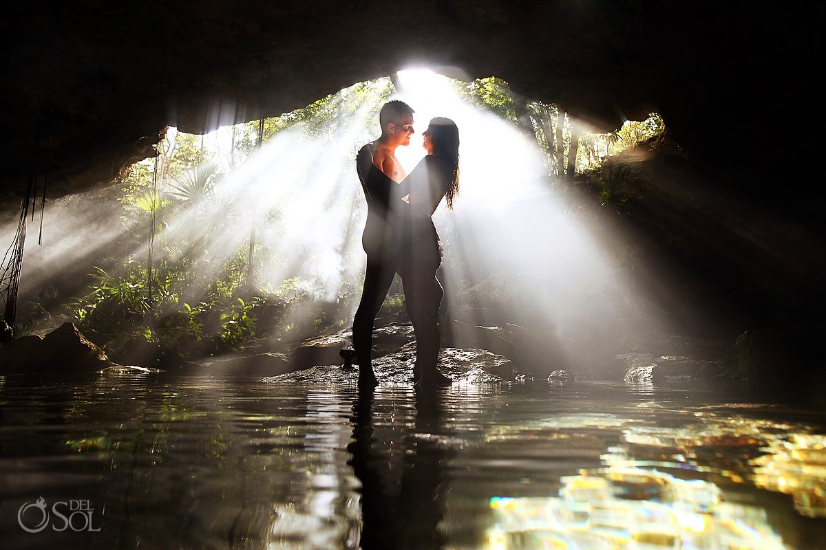 bride and groom stand naked in a cenote for trash the dress