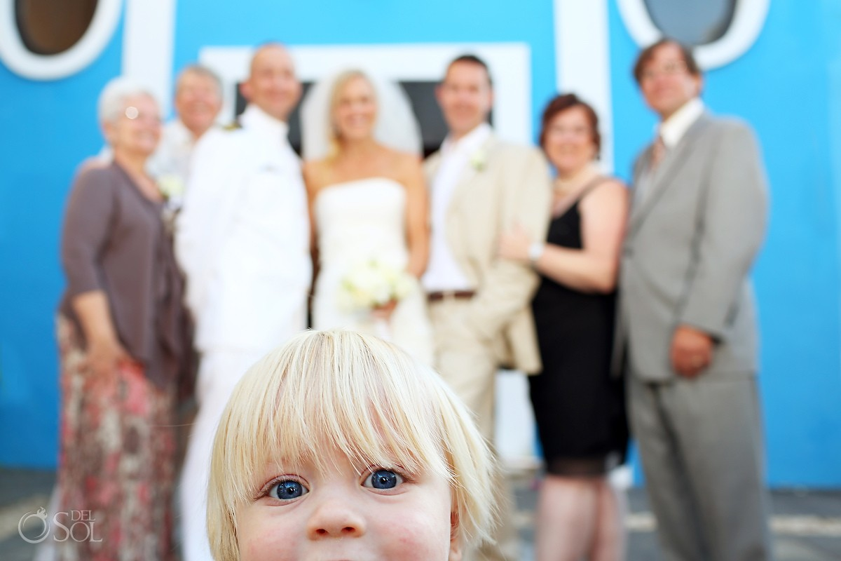 Child photobomb at beach wedding photo