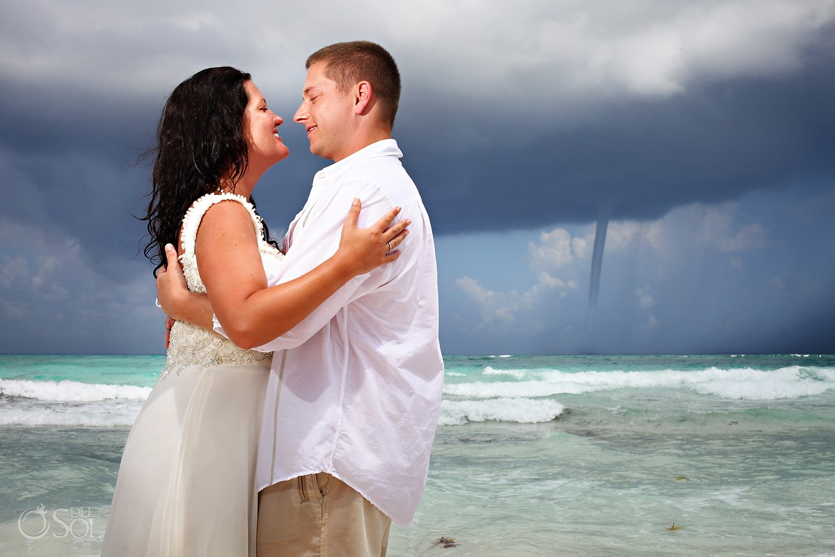 bride and groom stand next to water funnel at the beach in xpu ha mexico