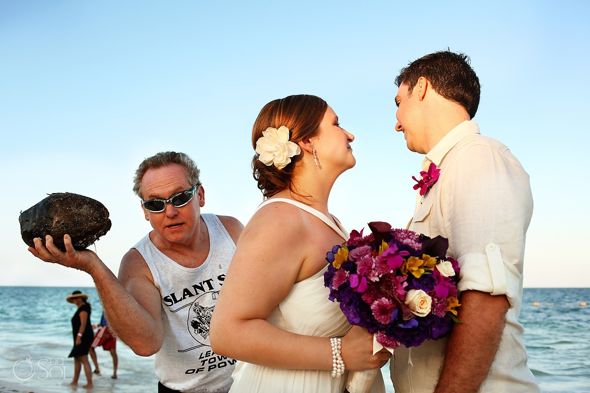 Man photobombs wedding portraits on the beach
