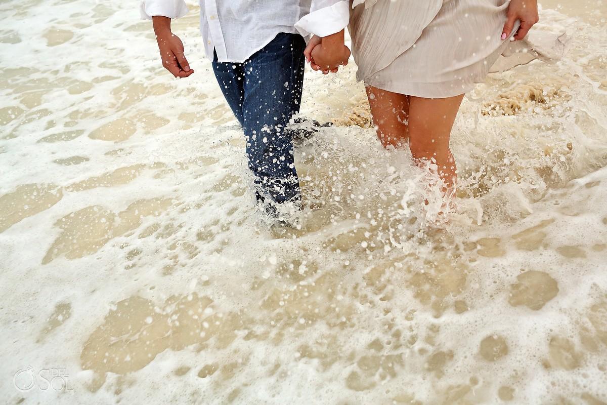 Couple running through the ocean playa del carmen mexico