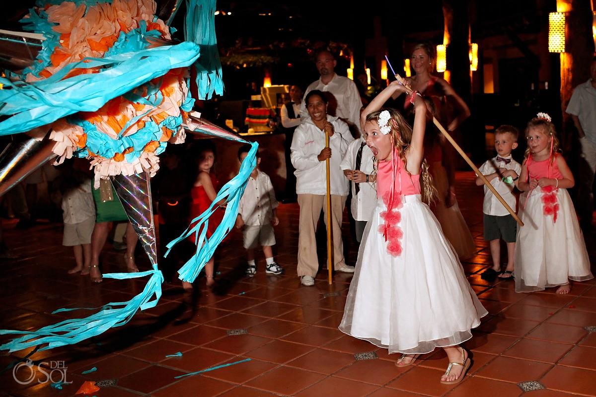 Small flowergirl hitting a pinata during a wedding reception at barcelo Maya