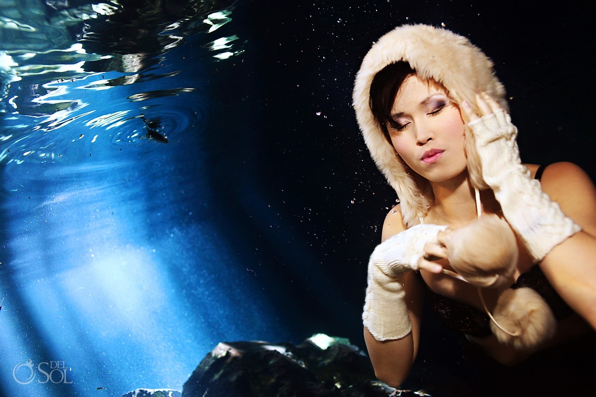 woman underwater wearing earmuffs and gloves