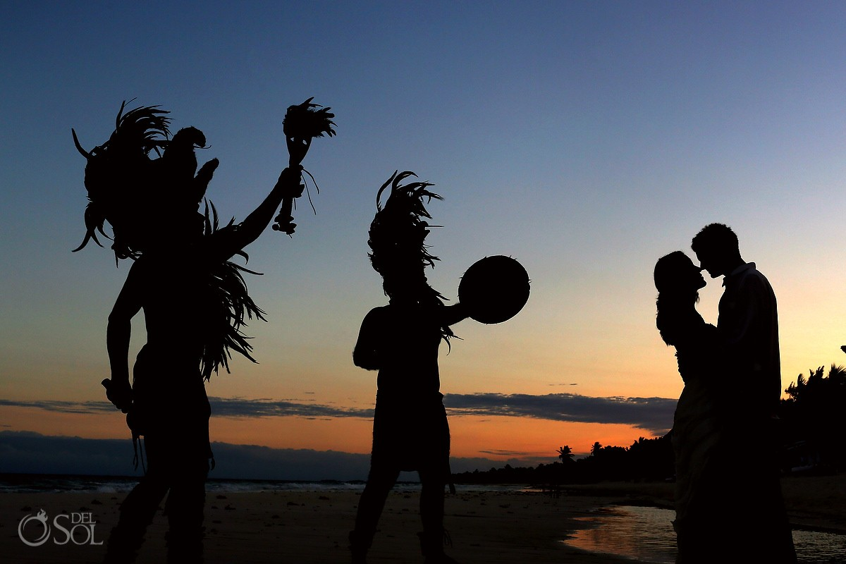 Mayan dancers in silhouette on the beach with kissing couple