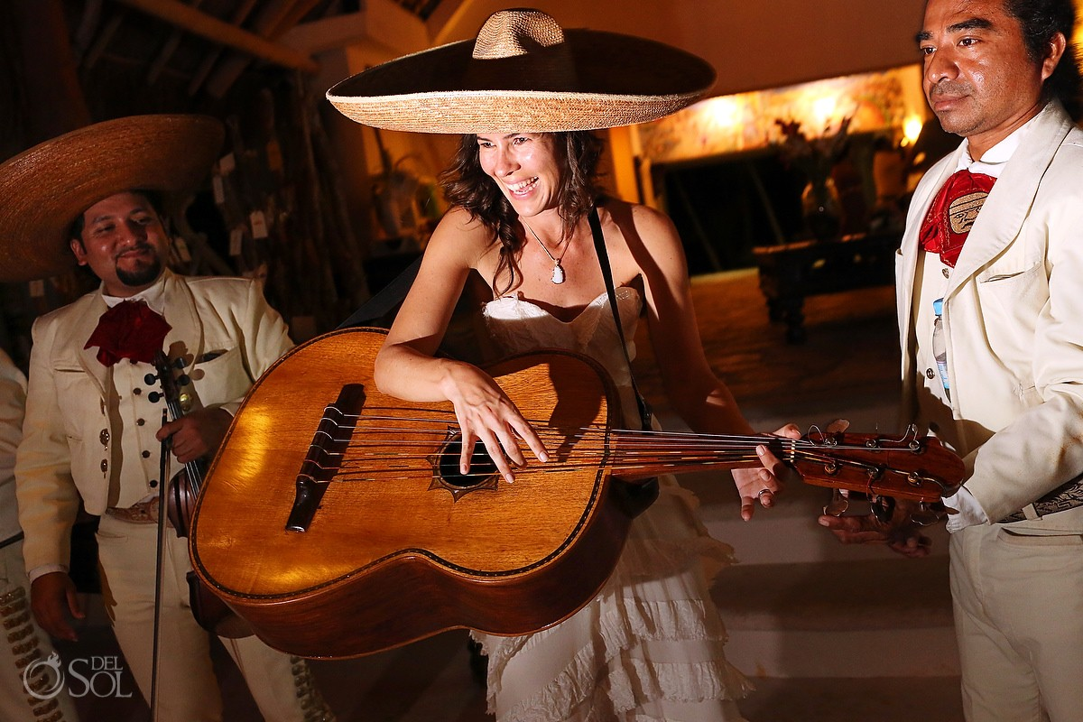 Bride playing guitar and wearing a Mexican sombrero