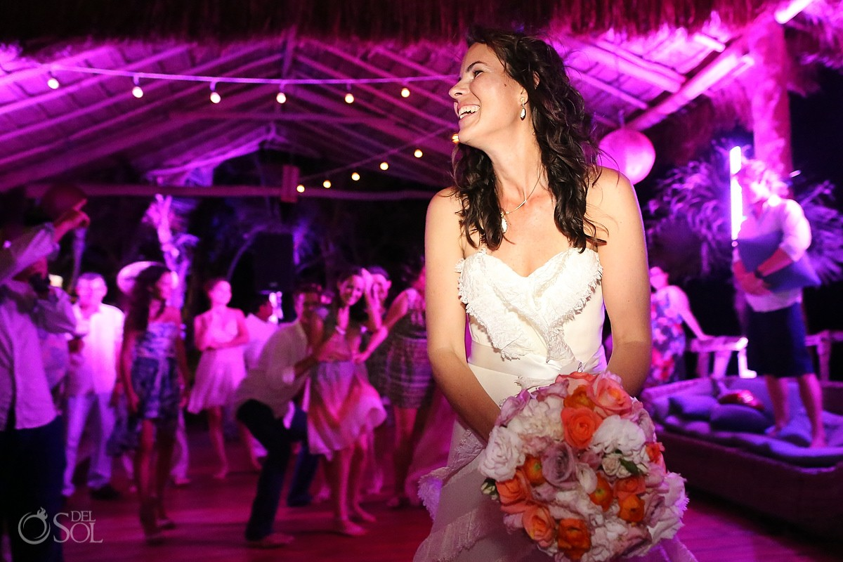 Bride throws bouquet pink lights palapa Tulum