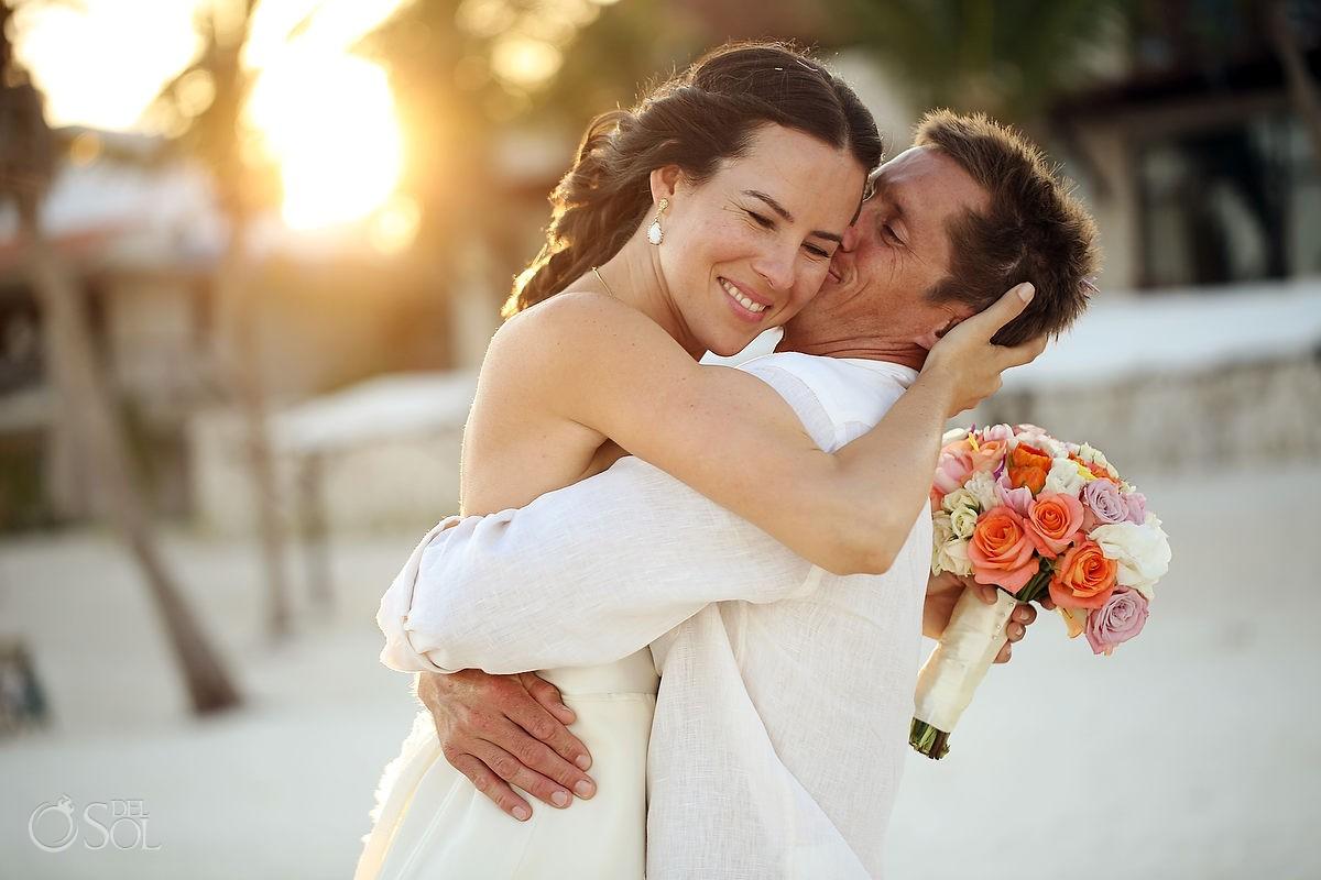 Sunset while groom kisses bride on beach