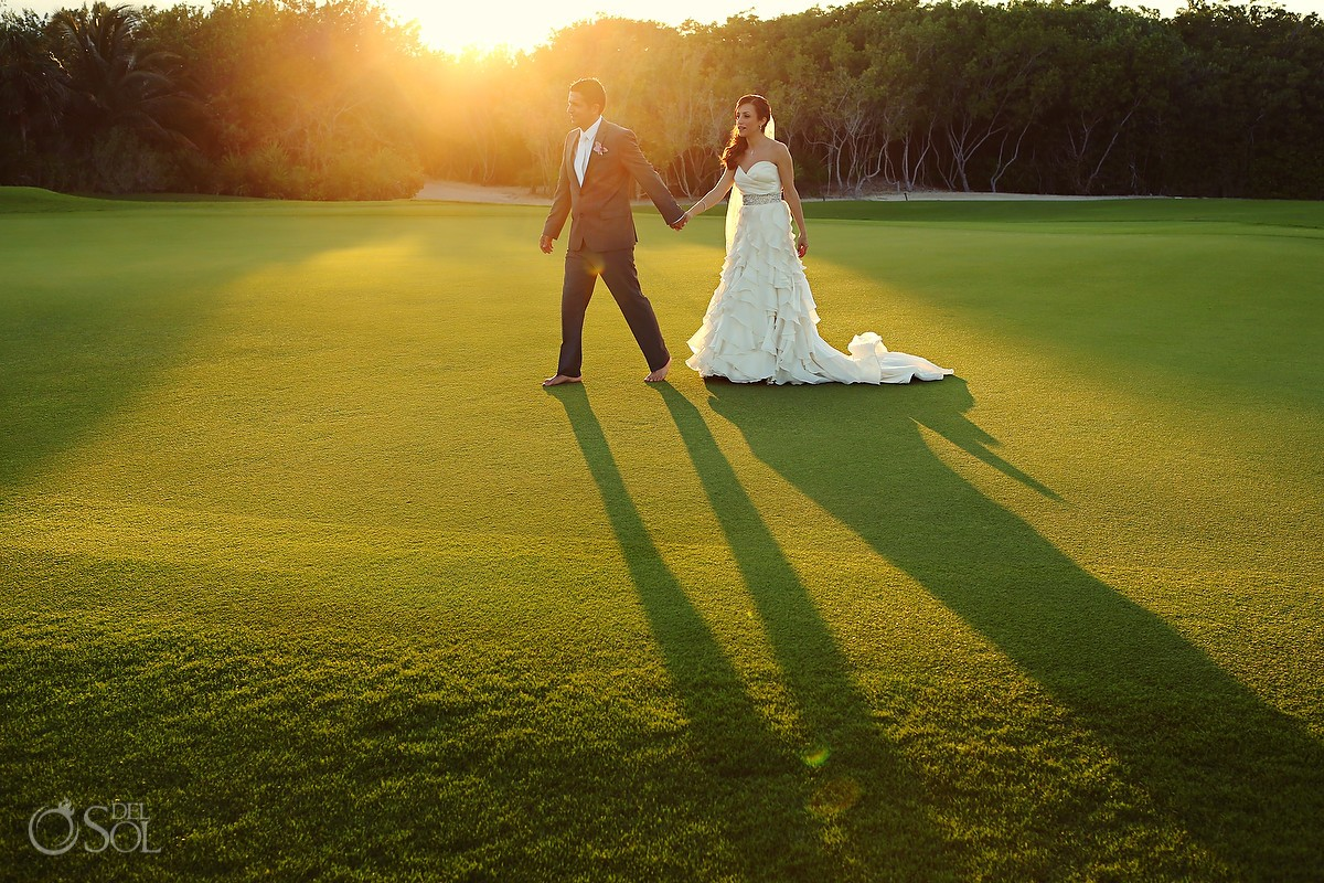 Bride and groom on golf course at sunset Riviera Maya