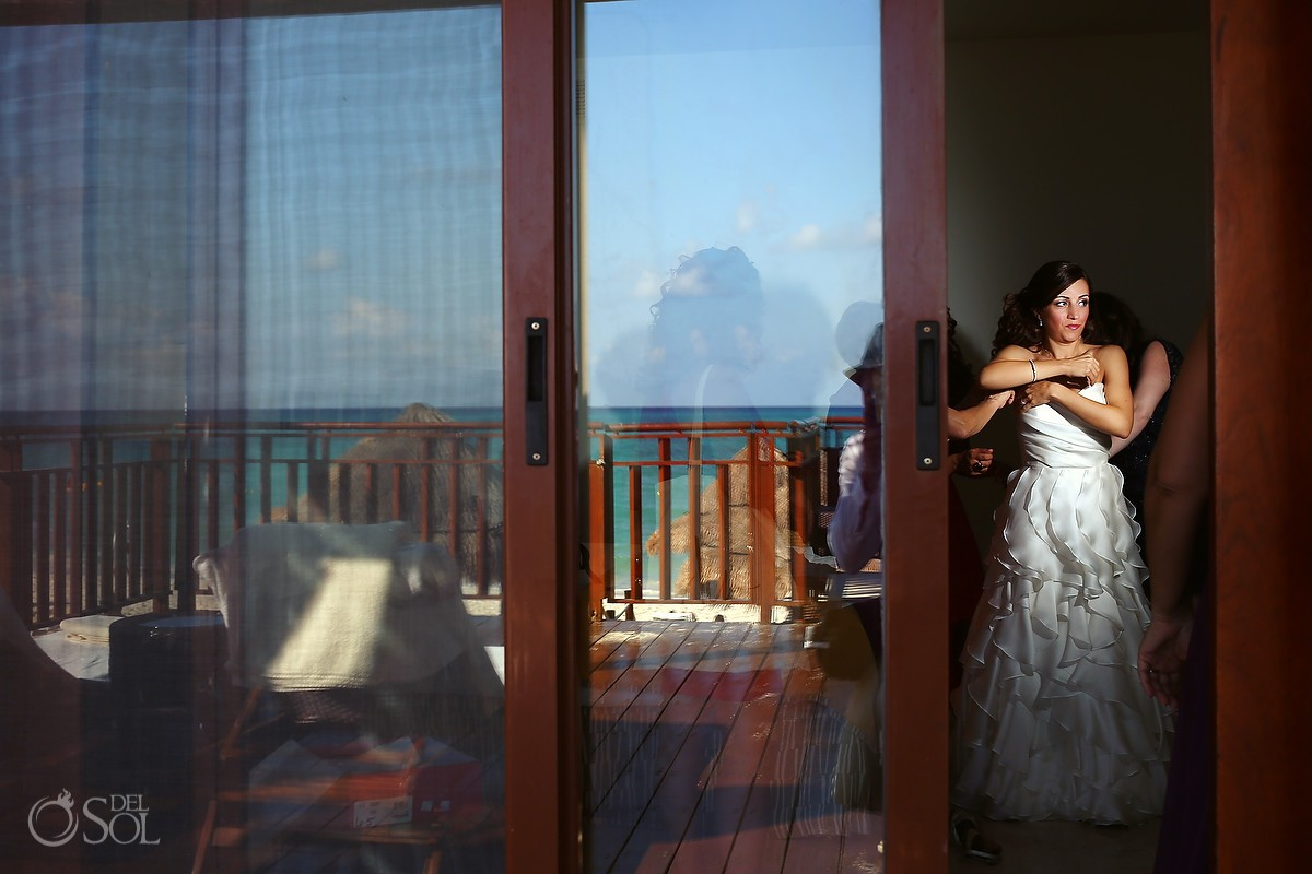Bride getting dressed with reflection of ocean