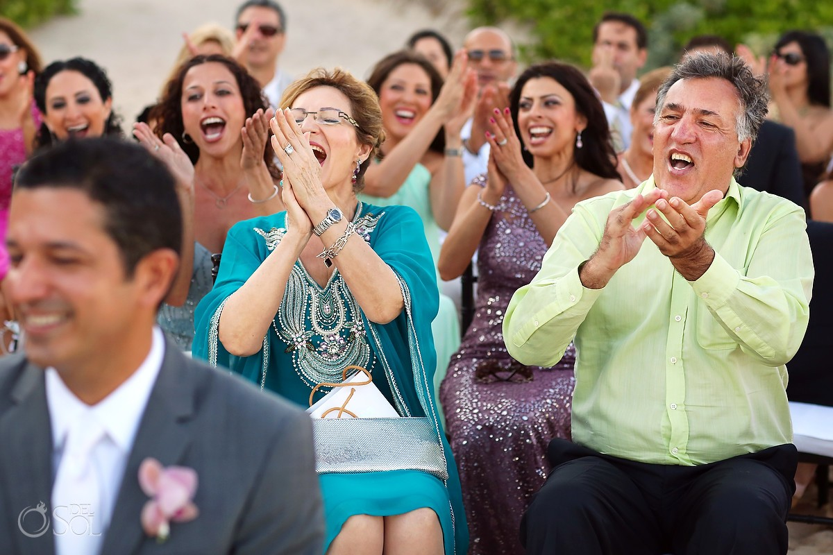 Happy wedding guests applaud and smile