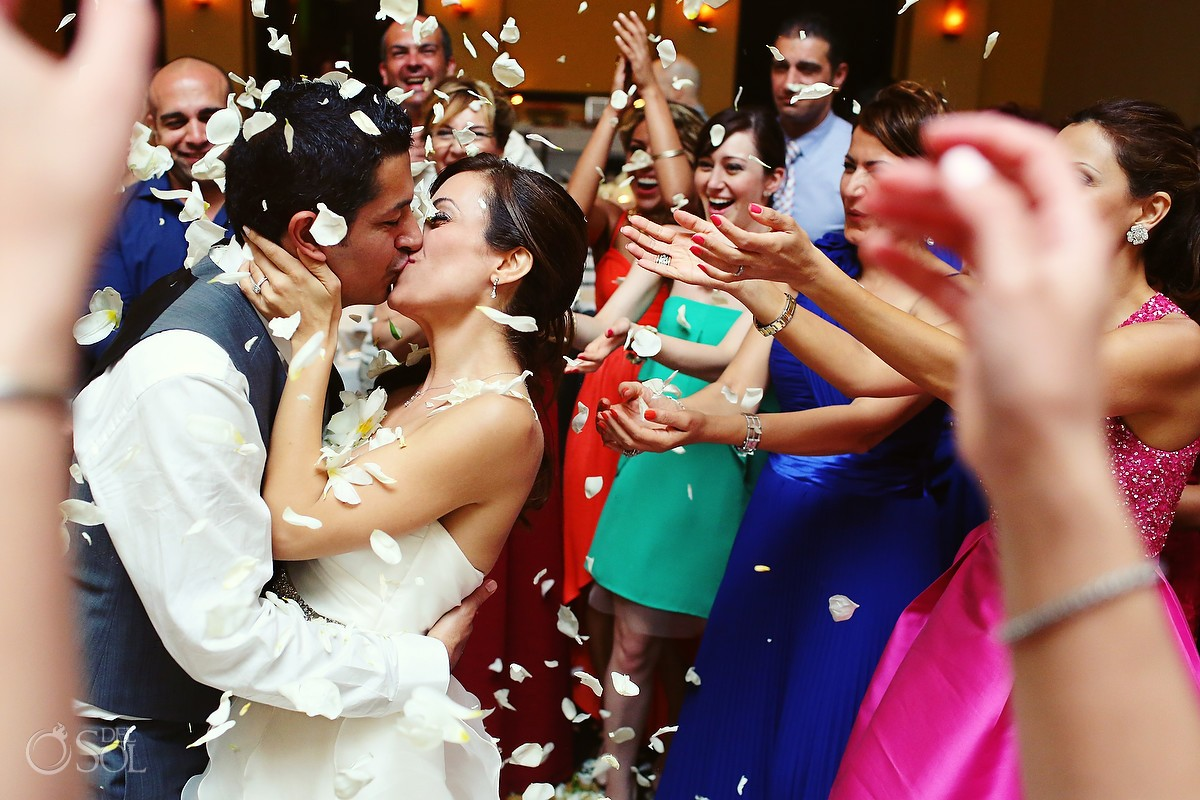 Throwing flower petals at a kissing bride and groom