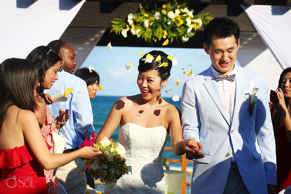 Bride and groom and flower petals beside the Mexican Caribbean Sea.