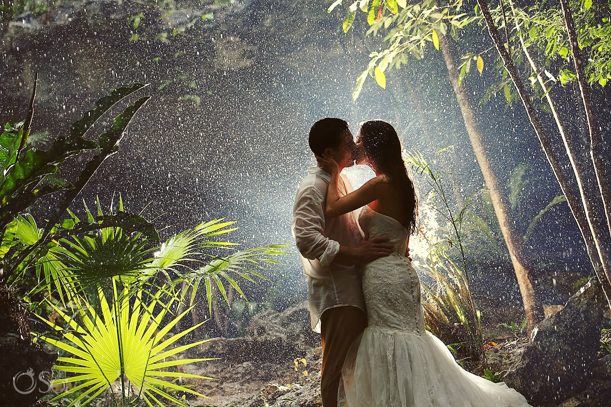 Bride and groom in the jungle under rain