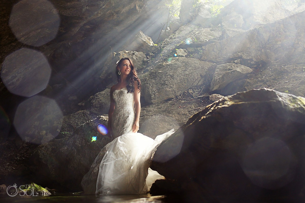 Bride in a cenote trash the dress shoot in a ray of sunlight
