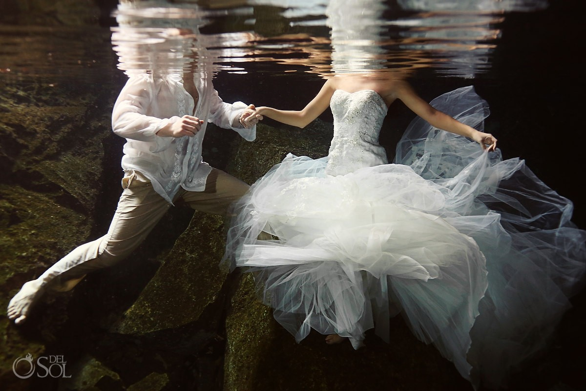 Bride and groom underwater in a cenote