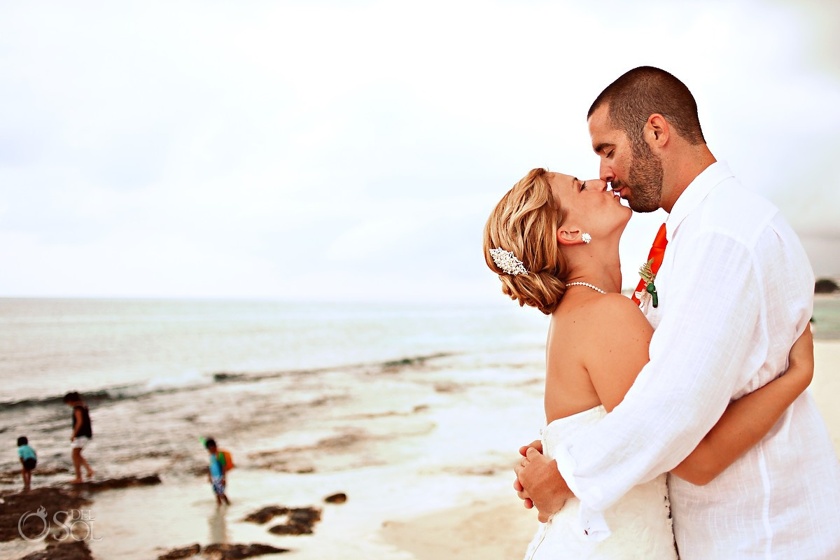 Bride and groom kissing on the beach in Mexico