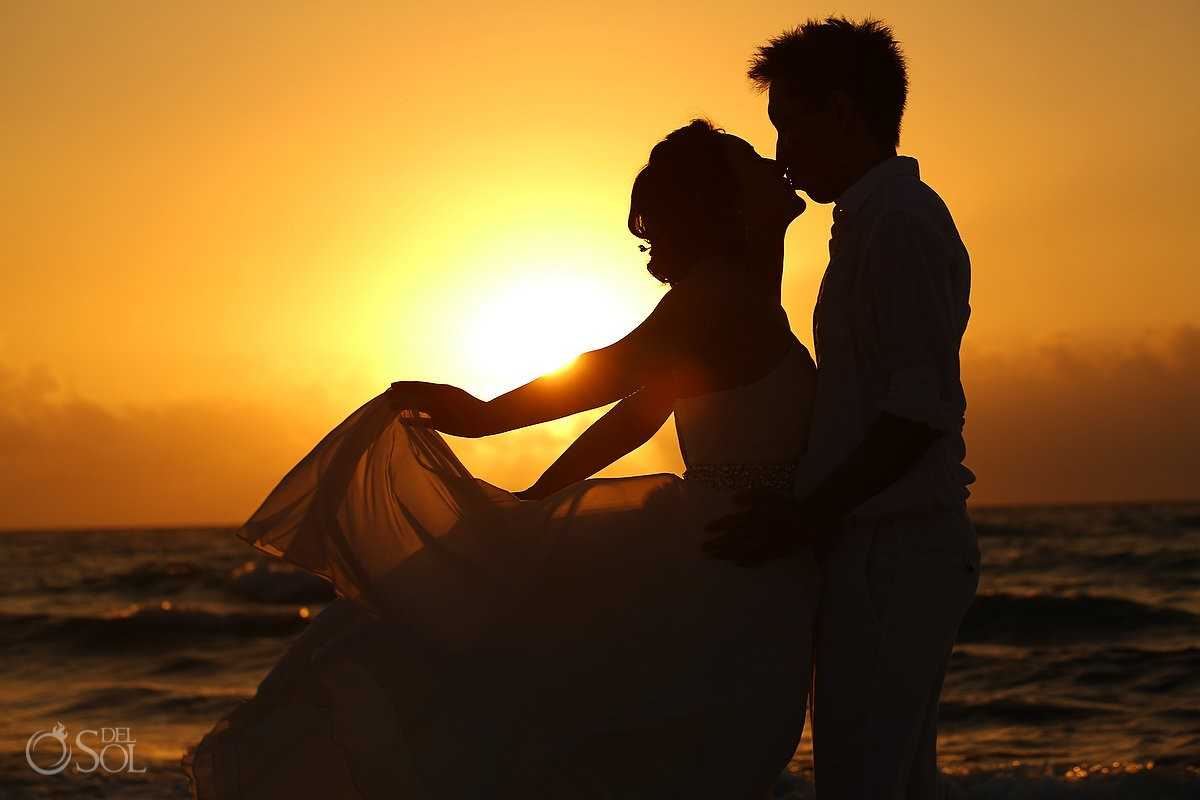 Silhouette sunrise bride and groom kissing