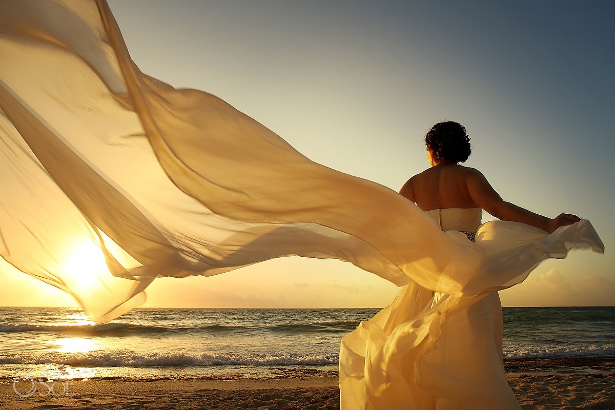 Flowing bridal gown on the beach at sunrise