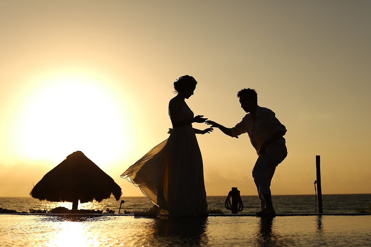 Sunrise silhouette of bride and groom