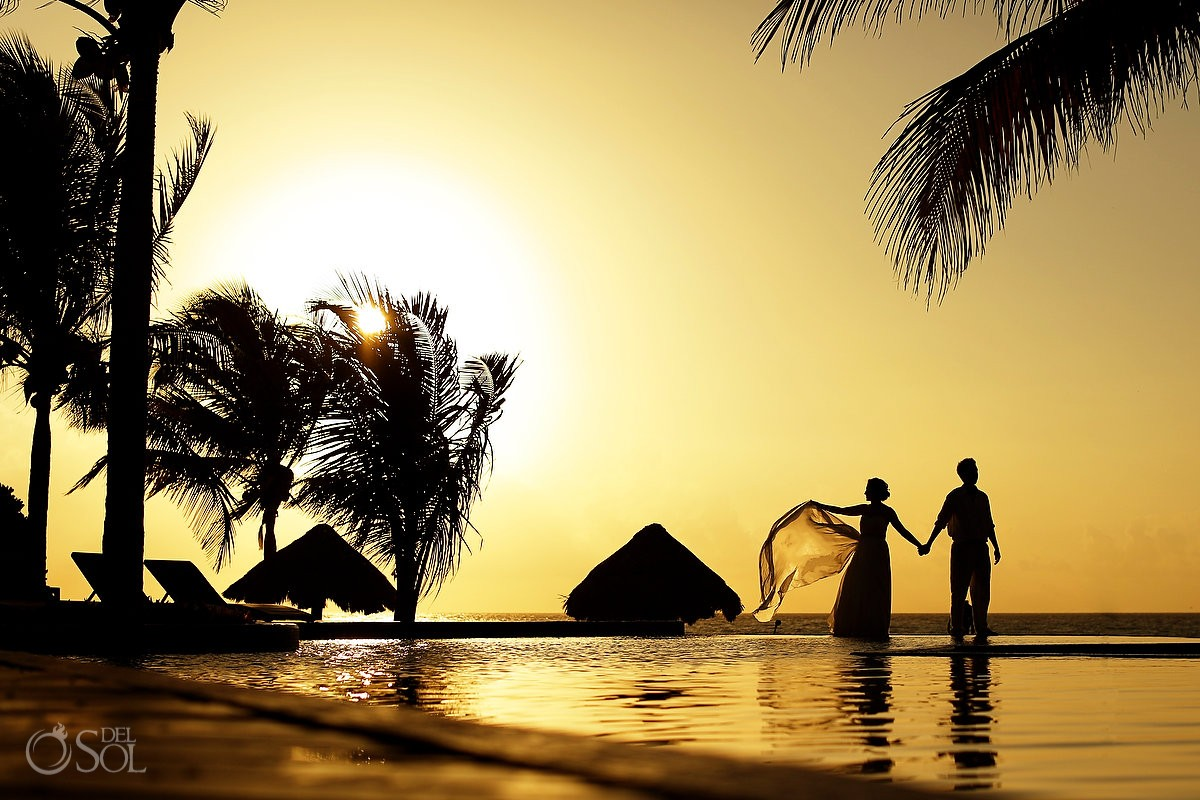 Bride and groom silhouette by the pool at sunrise Riviera Maya