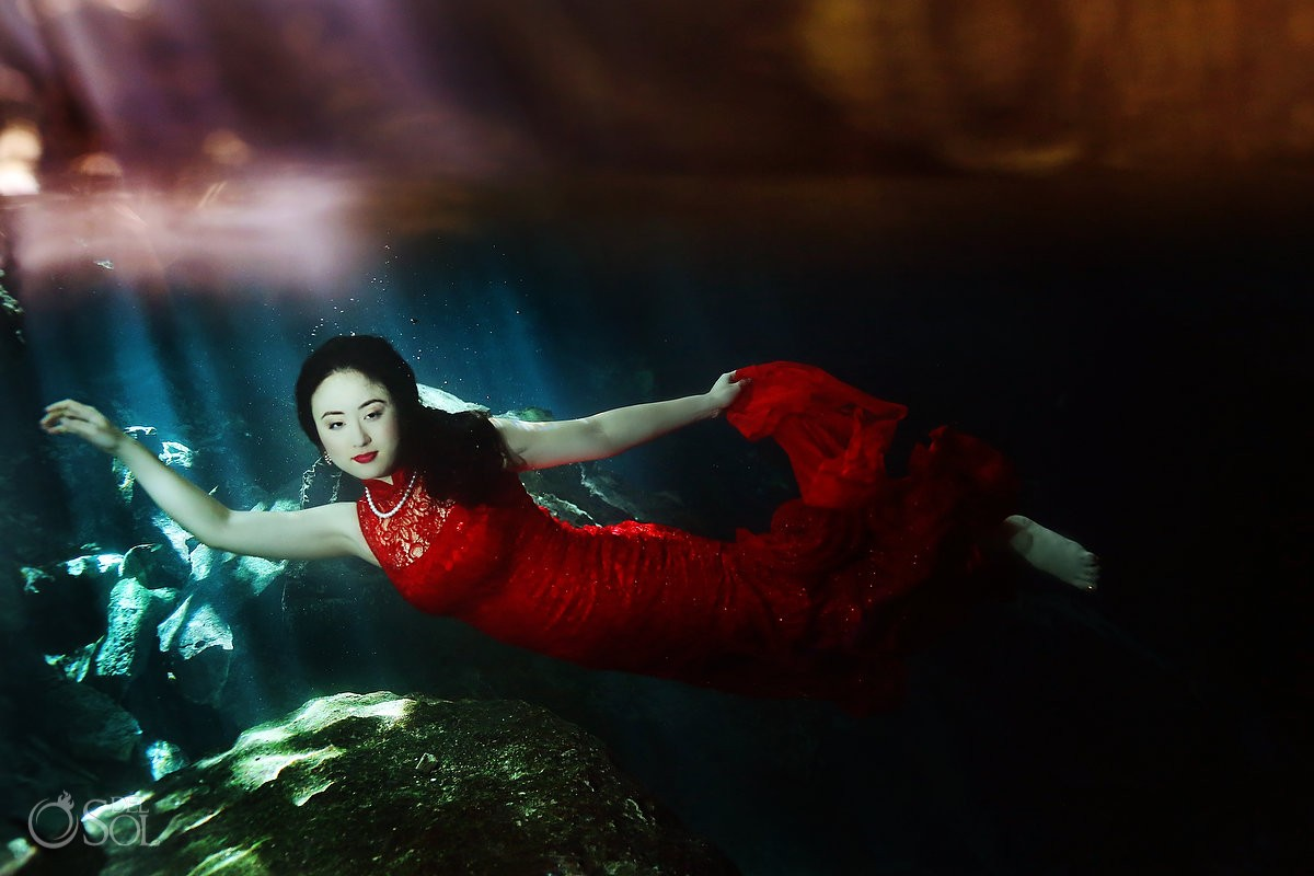 Chinese bride in red dress underwater in a cenote trash the dress