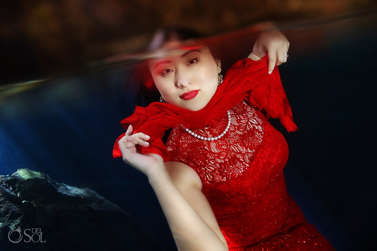 Chinese bride in red dress underwater