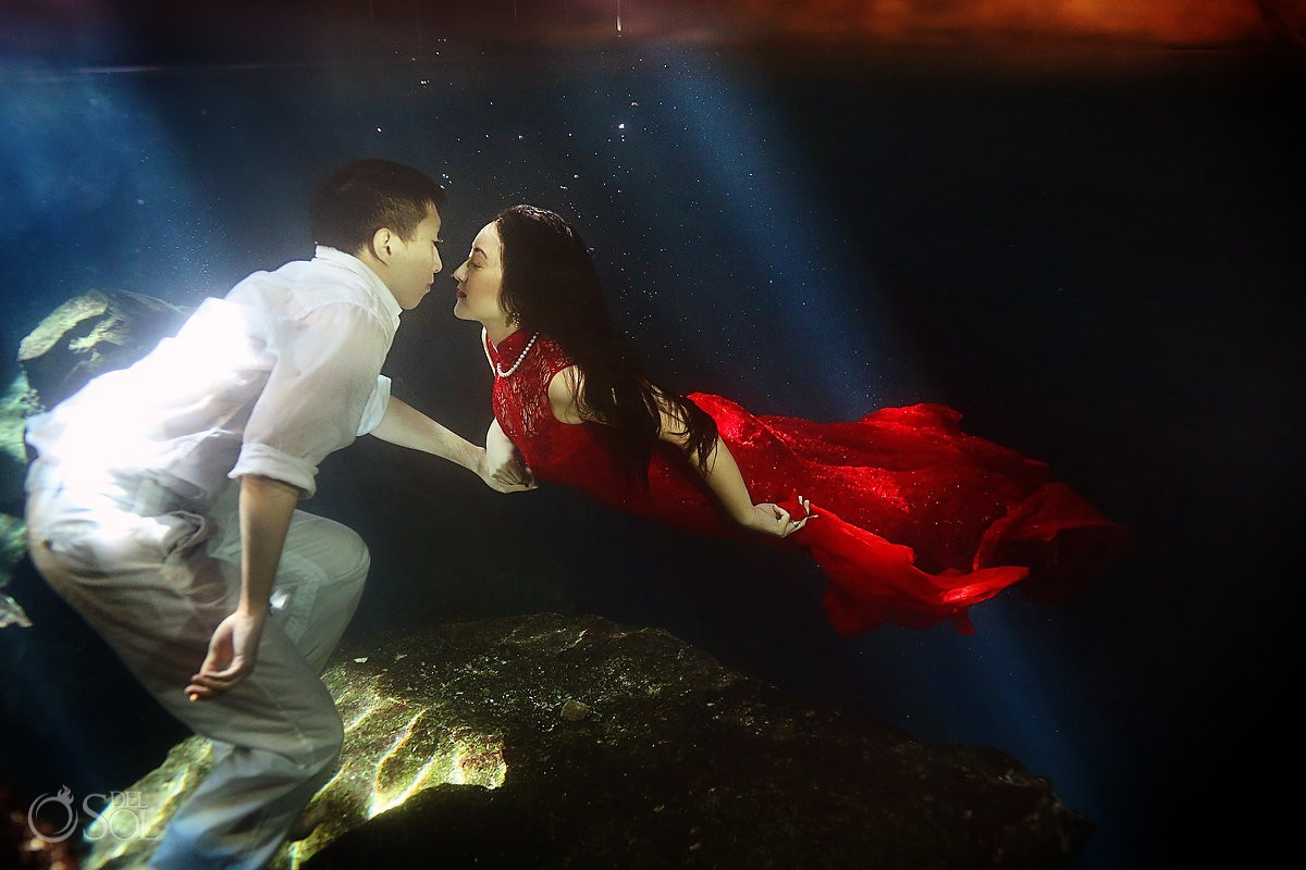 Underwater bride and groom in red dress in a cenote