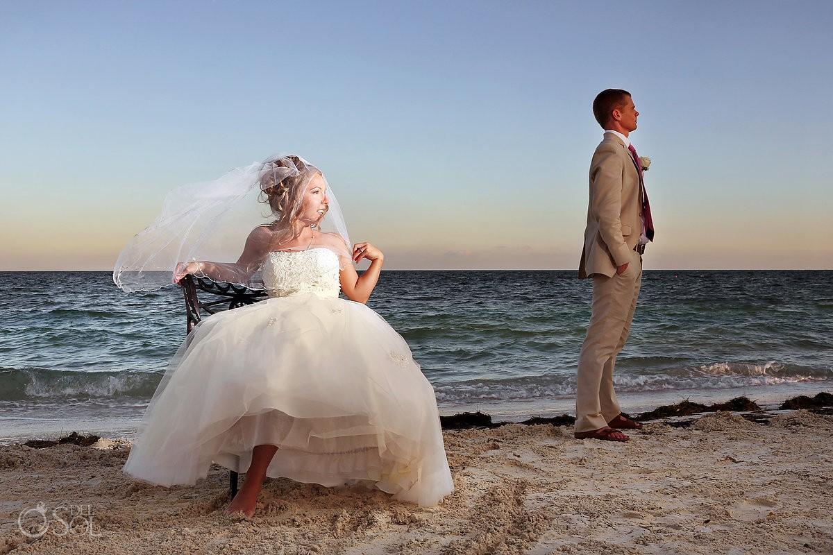 Beach wedding bride sitting in front of sea