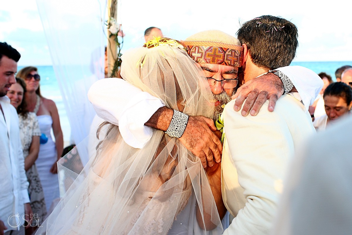 Shaman hugs bride groom Beach Cosmic wedding ceremony, Belmond Maroma Riviera Maya, Mexico