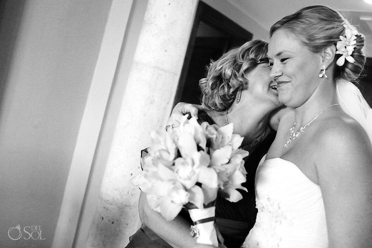 Mother of bride kissing the bride at a destination wedding in Mexico