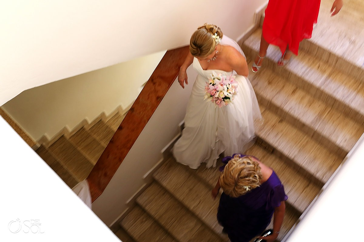 Bride going down stairs to her destination wedding in Mexico