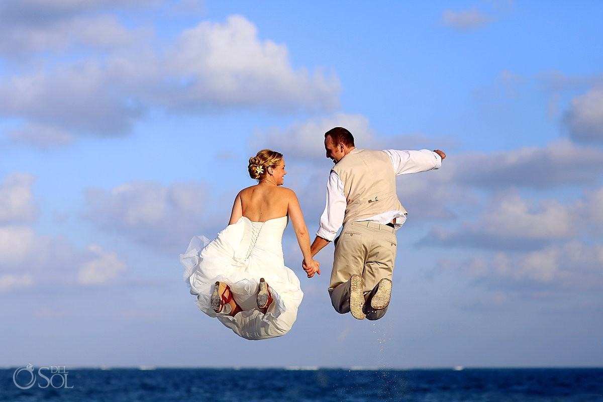 Bride and groom jumping on the beach at a destination wedding mexico