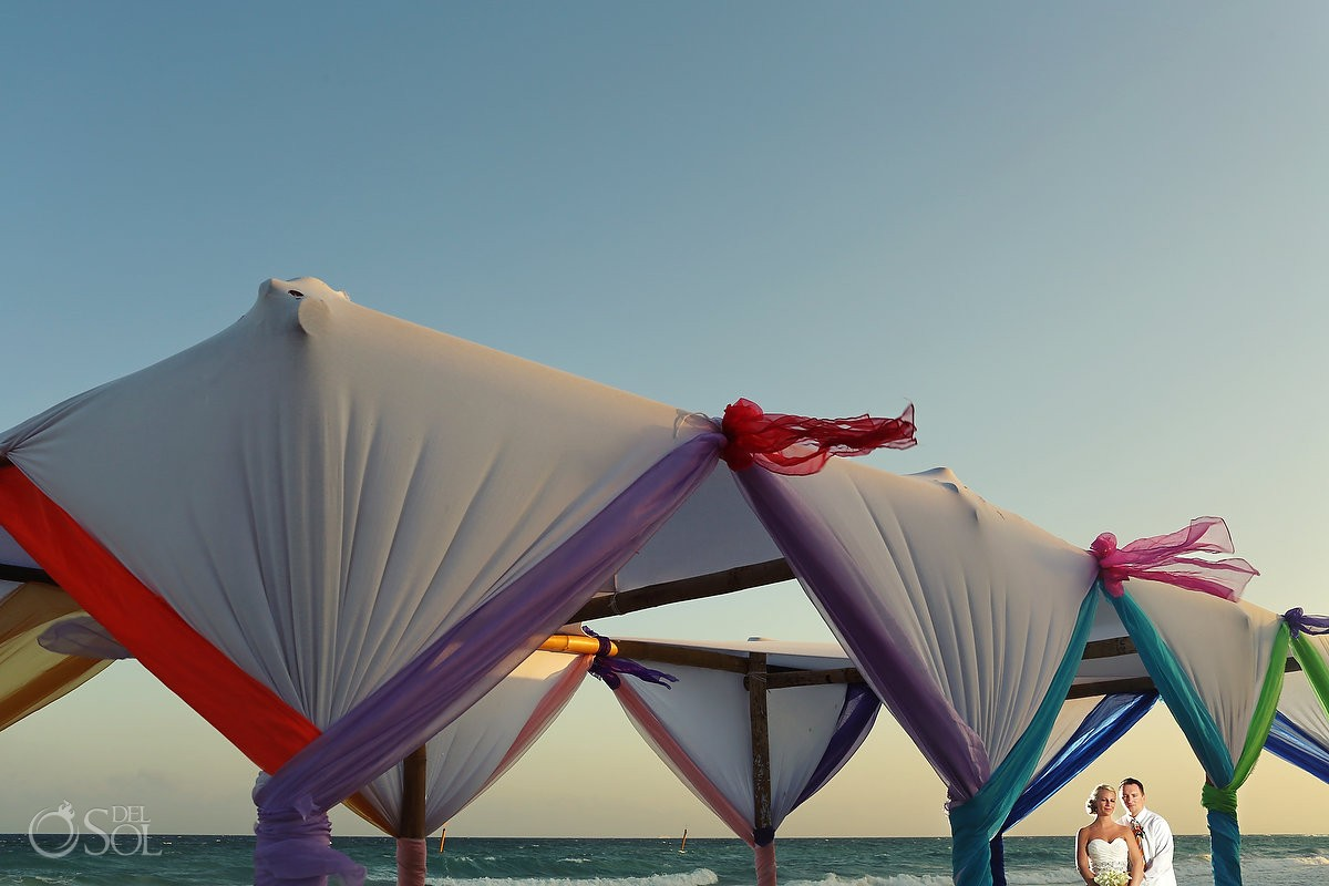Beach tent wedding photo with ocean bride and groom