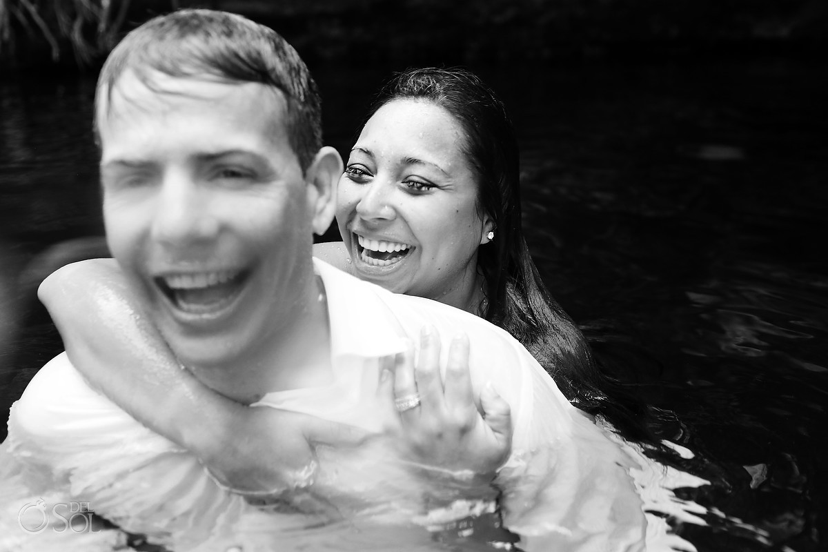 Laughing bride and groom in a cenote trash the dress photo shoot