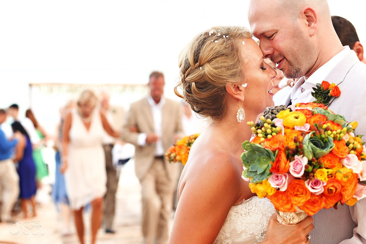 Bride and groom on the beach with orange bouquet