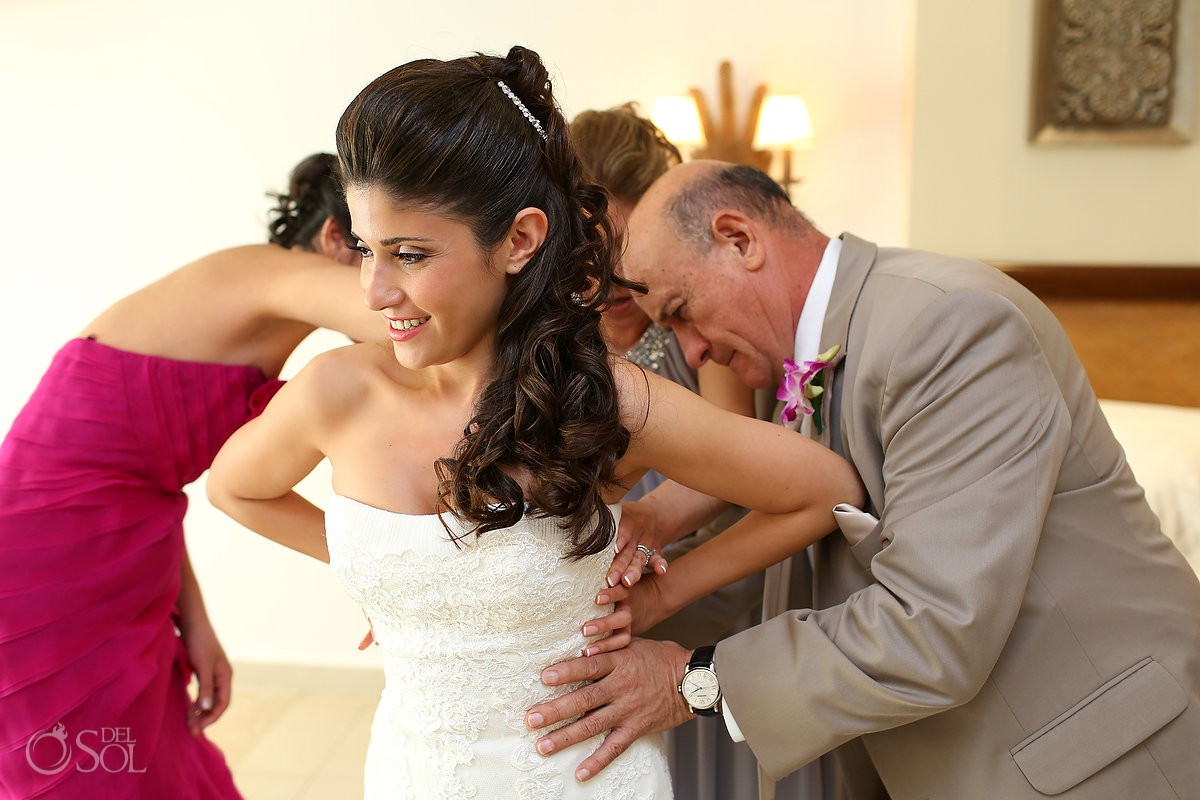 Father of the bride assisting with the dress