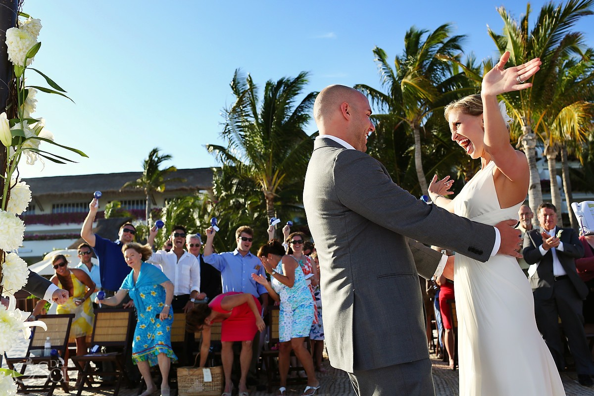 Bride and groom beach wedding with palm trees at the Grand Velas Resort Riviera Maya