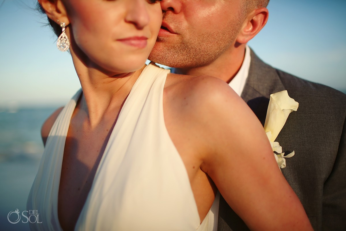 Groom kissing bride in the sun at Mexico beach wedding