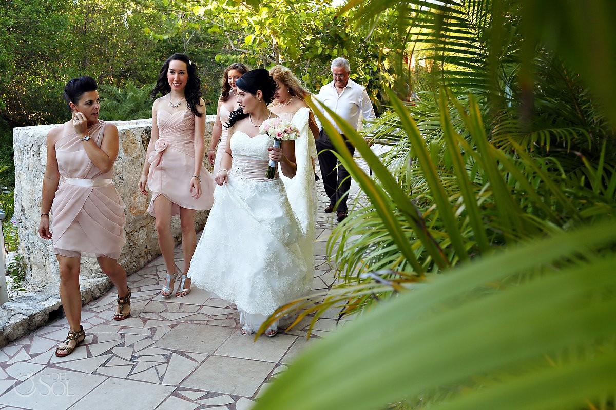 Bridal party walking down a path with jungle plants in Mexico destination wedding