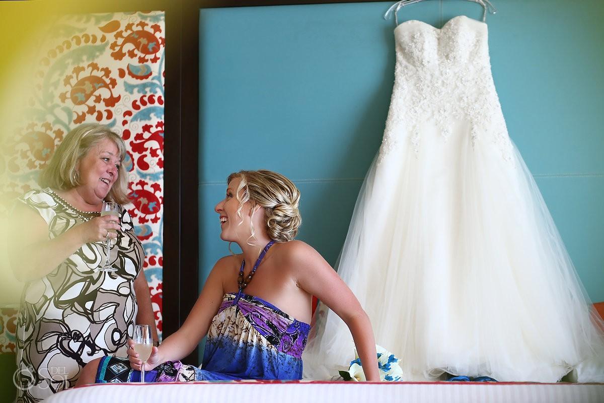 Bridal gown hanging behind bride on blue background