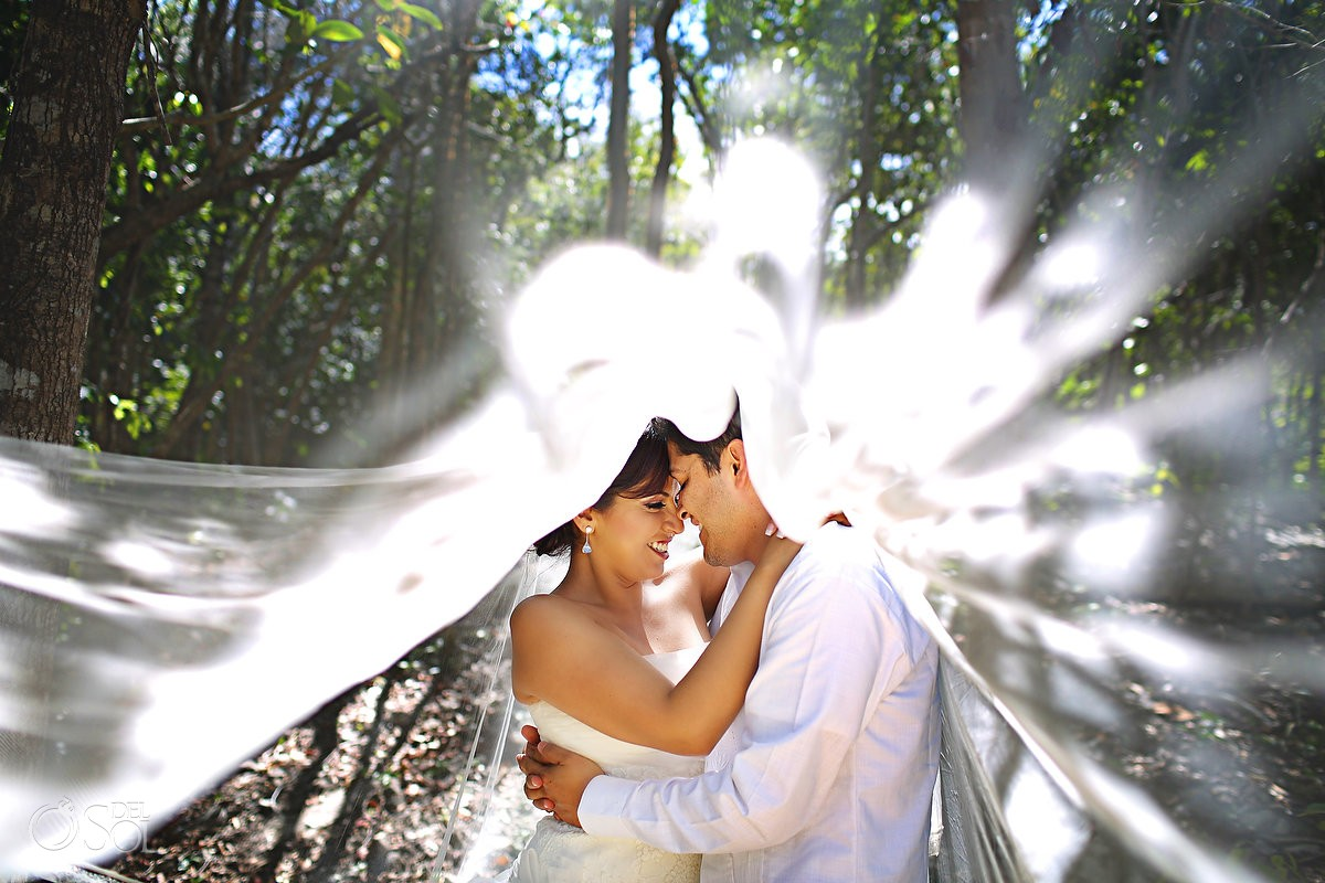 Bride and groom under a veil in the sun