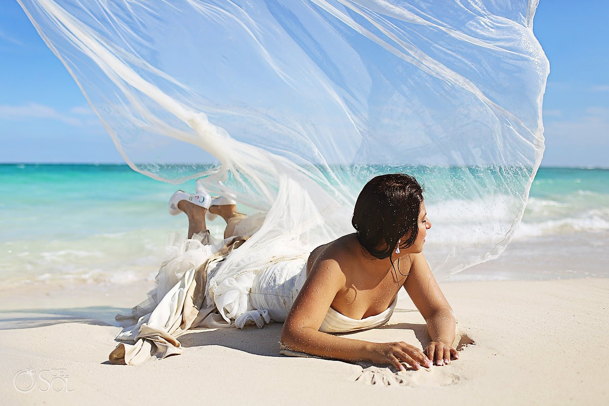 Bride lays on beach in a trash the dress in the Riviera Maya