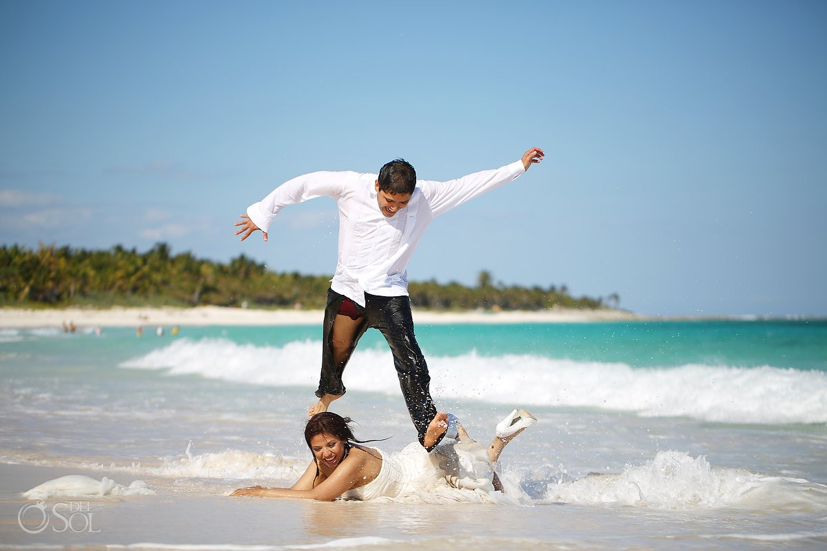 Groom jumps over the bride on the beach trash the dress Riviera Maya