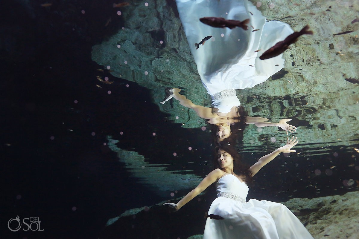 Underwater bride in a cenote with fish in a trash the dress photo shoot