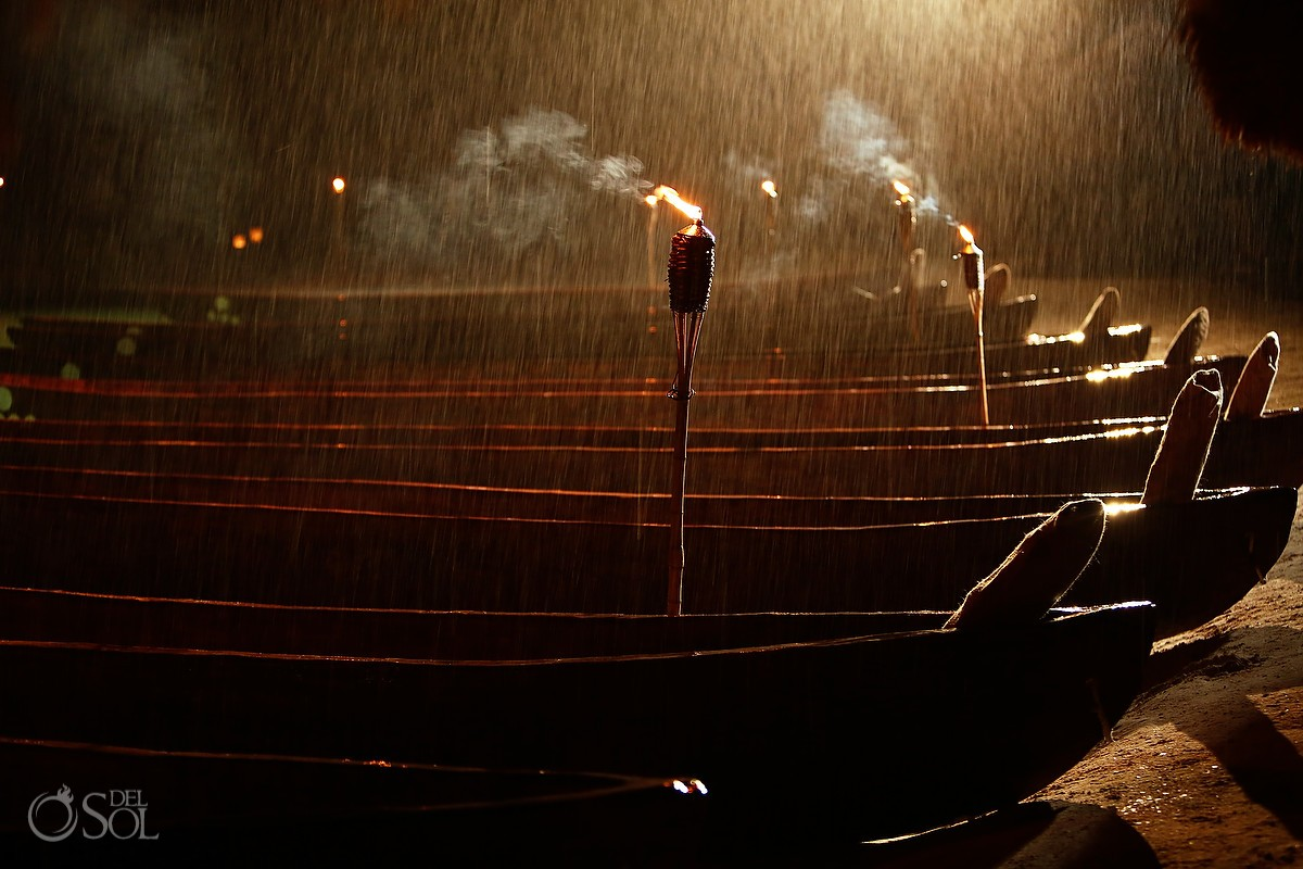 Torches in the rain over canoes