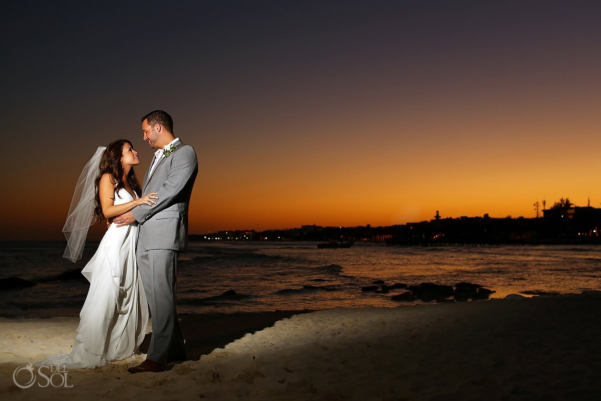 Bride and groom on the beach at sunset in Playa del Carmen, Mexico.