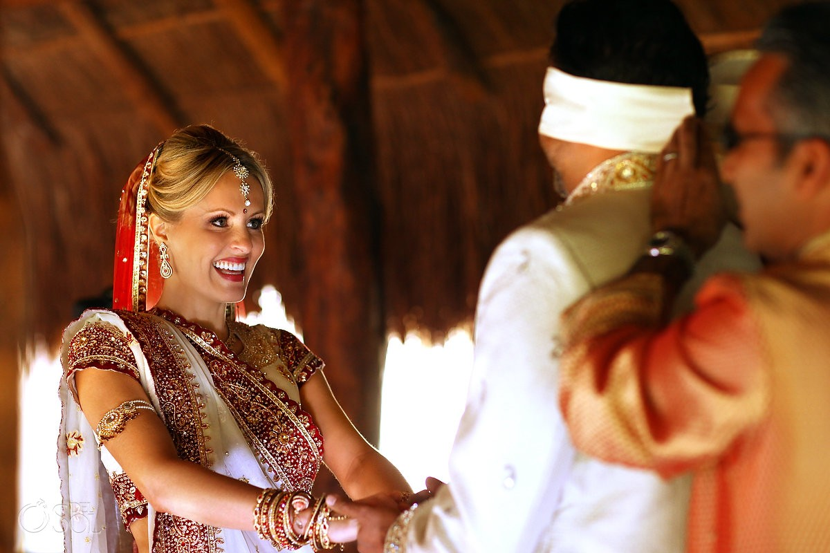Hindu wedding first look groom blindfolded before seeing blonde bride
