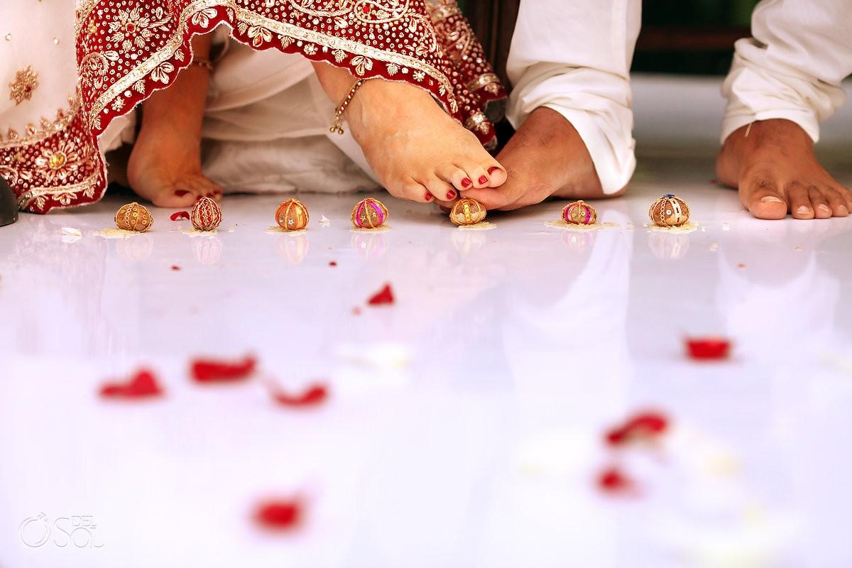 Saptapadi, the Seven Sacred Steps, bride groom feet rolling betel nut under toes Hindu wedding tradition