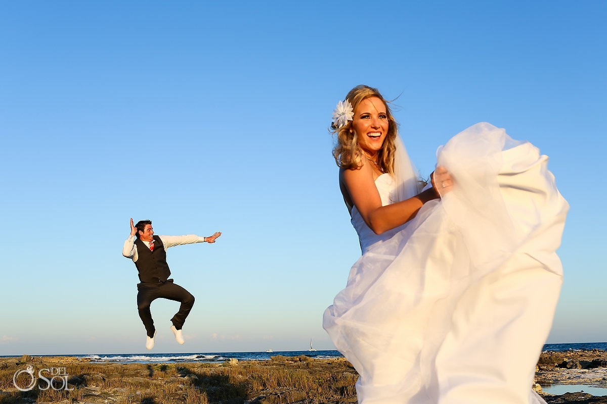 Beach bride and groom jumping smiling