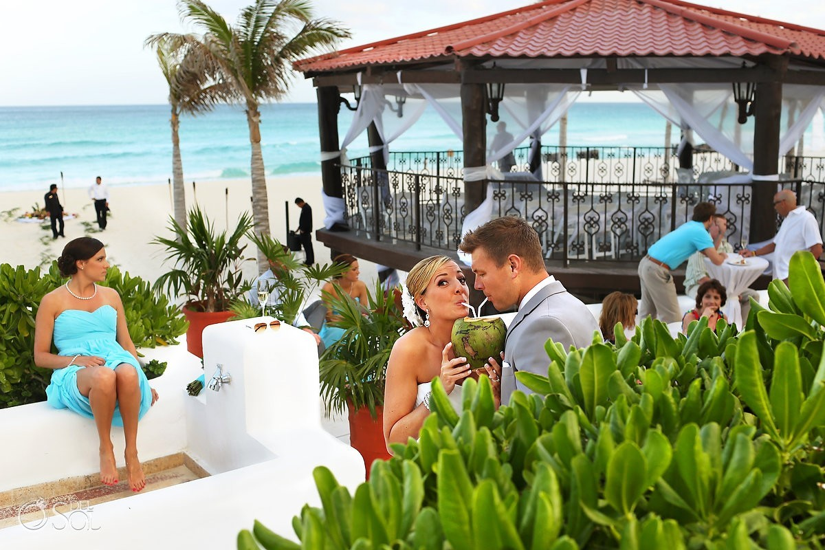 Cancun beach wedding bride and groom coconut drink